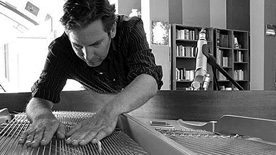 Andreas F. Staffel bending into a piano grand piano